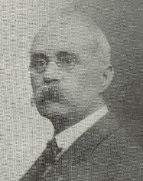 black and white photo of James Hard from shoulders up with wire rim glasses and a bushy mustache