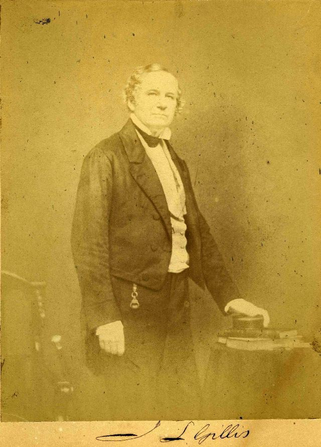 sepia tone photo of James L Gillis in black suit standing by small table